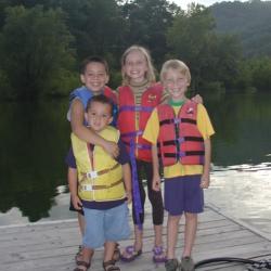 Children Smiling on Deck Near Lake
